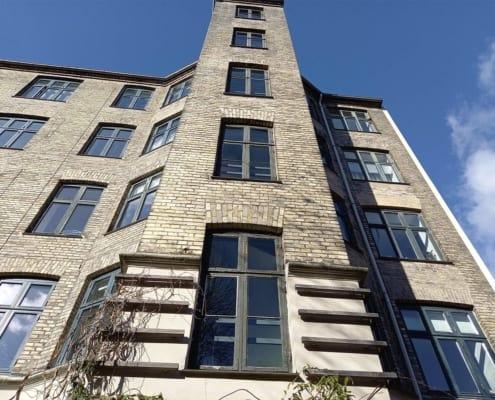 etageejendom med vinduer og mursten